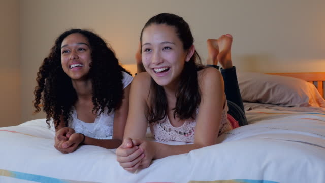 teenage girls watching television on bed - piedi alzati video stock e b–roll