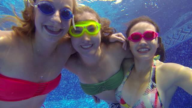Teenage girls with goggles looking underwater