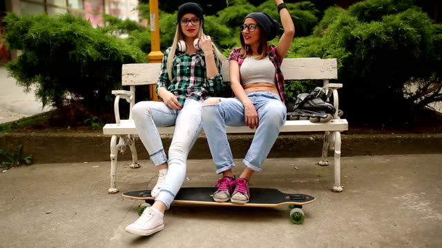 Teenage girls with skateboard having great time outdoors