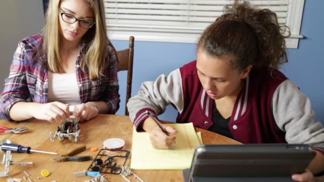 adolescente ragazze lavorano su un progetto di robotica - varsity jacket video stock e b–roll