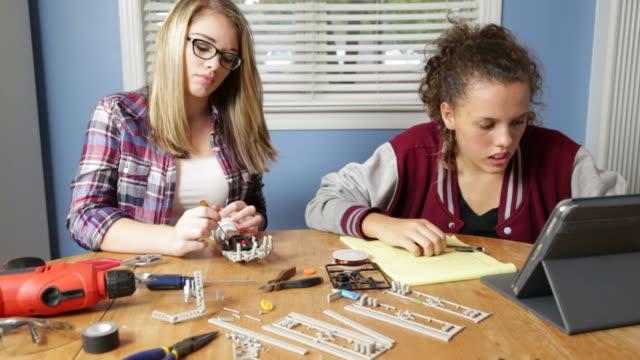 adolescente ragazze lavorano su progetto di robotica - varsity jacket video stock e b–roll