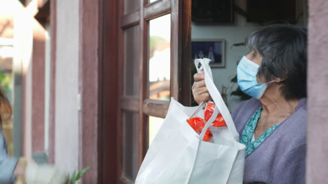 teenage girl,volunteer,delivering groceries to a senior woman, insulation,covid 19 - determinazione video stock e b–roll