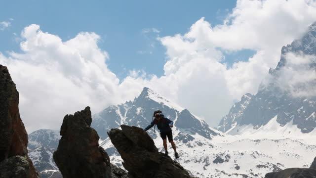pan of teenage hiker ascending to highest pinnacle - one teenage boy only stock videos & royalty-free footage