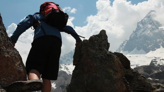 pan of teenage hiker ascending to pinnacle summit - one teenage boy only stock videos & royalty-free footage