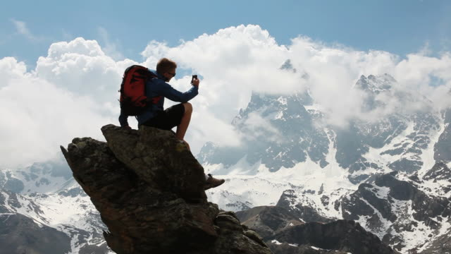 PAN of teenage hiker taking picture from pinnacle summit