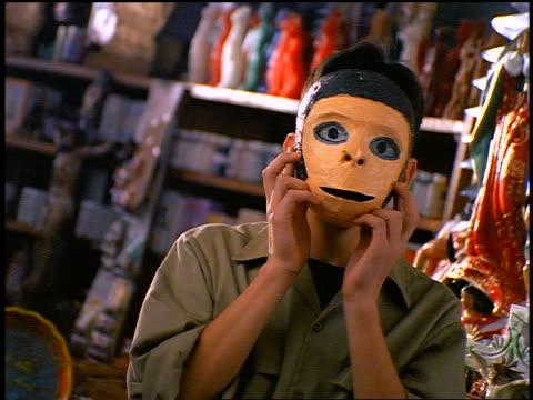 PORTRAIT teenage Hispanic boy taking off mask + smiling
