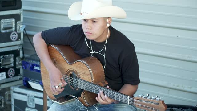 ragazzo ispanico adolescente che indossa un cappello da cowboy che suona la chitarra - musica country video stock e b–roll