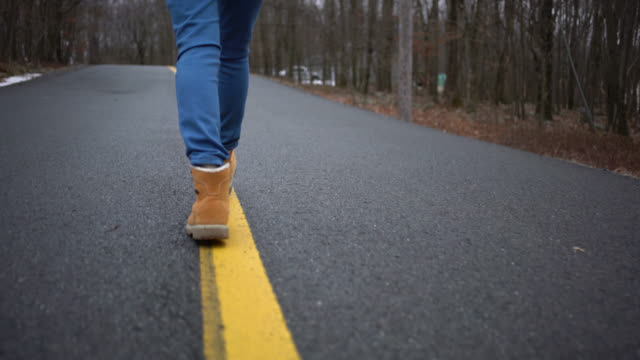 Teenage in the yellow boots walking on the road