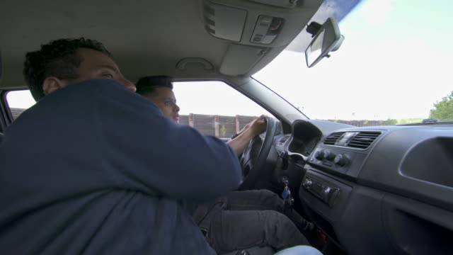 Teenage learning to drive car with father