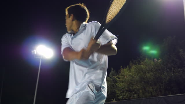 vídeos de stock, filmes e b-roll de ms teenage male tennis player hitting backhand while practicing on outdoor court at night - só um menino adolescente