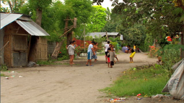 WS Teenage males teens playing basketball on neighborhood dirt road male doing backflip male shooting ball toward basket attached to roadside tree...