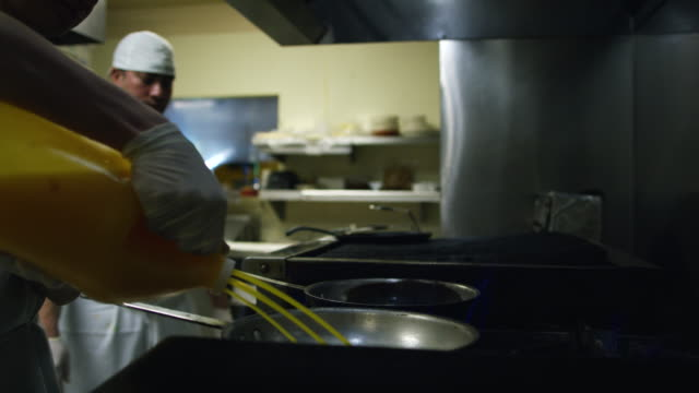 teenage mexican cook pours oil into pans next to a mexican cook in his thirties on a commercial range at a mexican restaurant - mexican restaurant stock videos & royalty-free footage