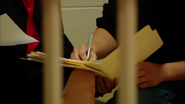 cu teenage prisoner signing documents for lawyer in cell/ lawyer getting up and being let out of cell by prison guard/ new jersey - lawyer stock videos & royalty-free footage