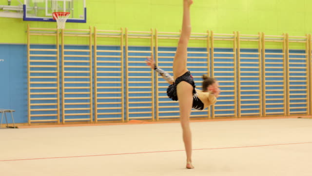 teenage rhythmic gymnastics athlete doing a pirouette - persona di sesso femminile video stock e b–roll
