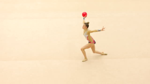teenage rhythmic gymnastics athlete practicing with ball - persona di sesso femminile video stock e b–roll