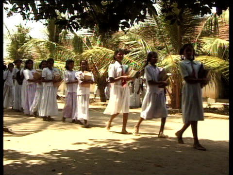 teenage school girls carrying books walk in line from school sri lanka - schoolgirl stock videos and b-roll footage