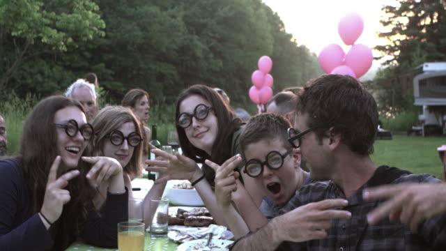 stockvideo's en b-roll-footage met tiener selfie partij grote familie buiten - jubileum