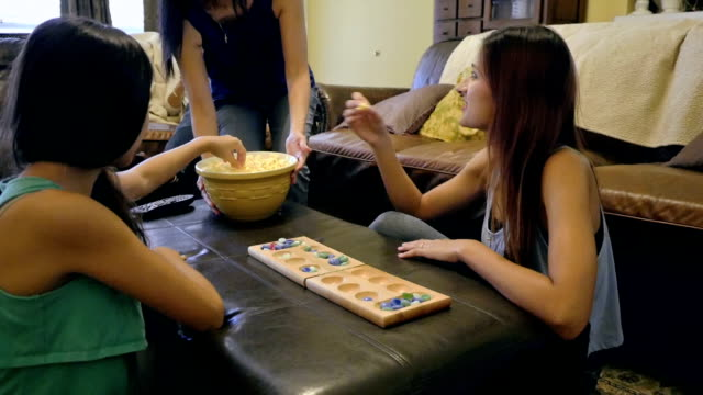 Teenage sisters playing board game at home, mom serving popcorn