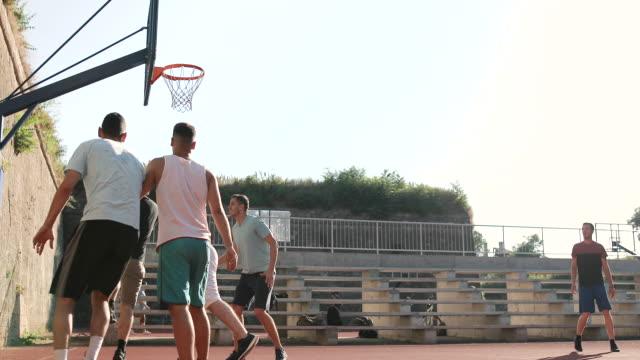 vidéos et rushes de amis sportifs adolescents pratiquant le jeu de streetball sur le court extérieur. joueur de streetball plaçant un écran sur le défenseur et prenant le projectile facile de saut tout en jouant le jeu sur le terrain de basket-ball sur la rue. - streetball