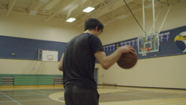 teenage student dribbling basketball in school gym - gym stock videos & royalty-free footage