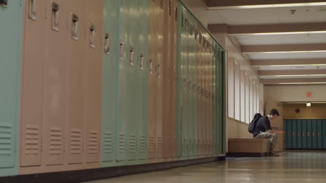 teenage student sitting alone in a school hallway - teenagers only stock videos & royalty-free footage