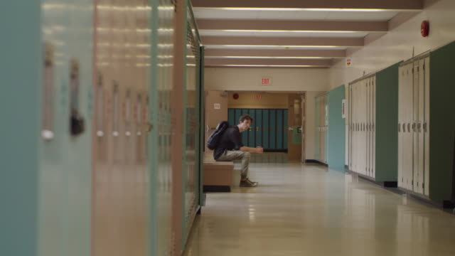 Teenage student sitting in empty school hallway