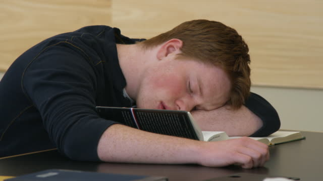 CU DS Teenage student sleeping on desk with book, Orem, Utah, USA