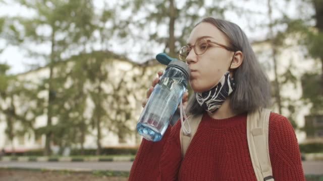teenage student wearing reusable protective face mask and drinking water - bottle stock videos & royalty-free footage