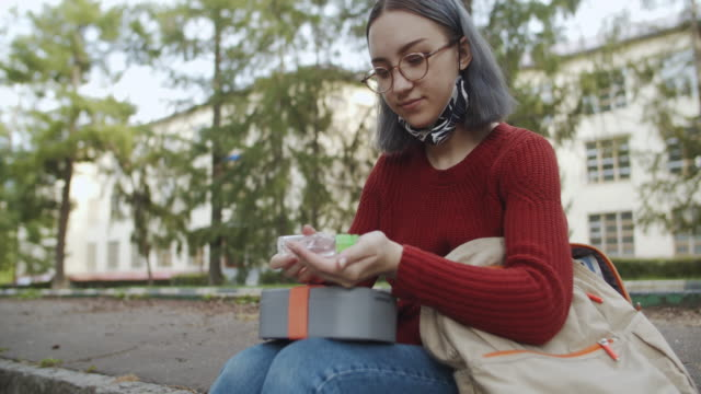 teenage student wearing reusable protective face mask and using hand sanitizer before eating lunch - back to school stock videos & royalty-free footage