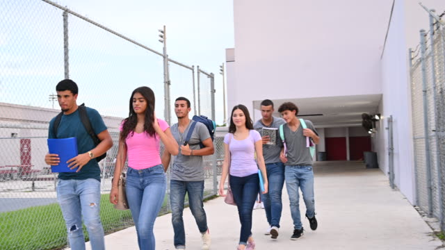 teenage students walking together outside school - secondary school child stock videos & royalty-free footage