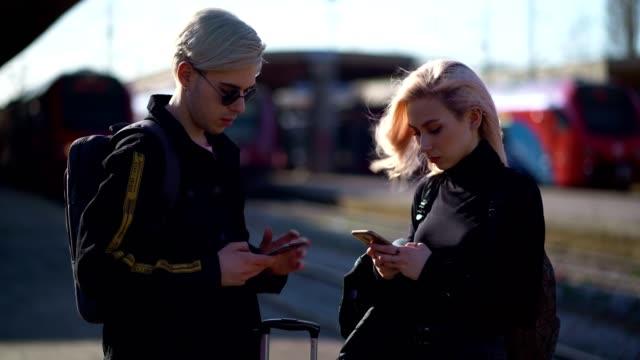スマートフォンを使用して十代の旅行者 - 鉄道のプラットホーム点の映像素材/bロール