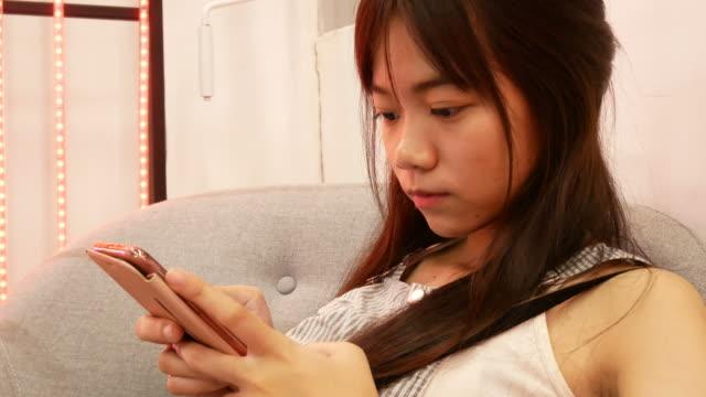 vídeos y material grabado en eventos de stock de mujer adolescente chat maseage en el teléfono inteligente - sólo una adolescente