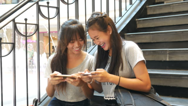 teenage women using smart phone in university