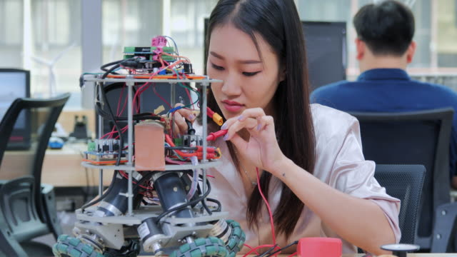 teenage women works on a fully functional programable robot for school robotics club project.creative designer testing robotics prototype in workshop.education,technology,teamwork,science and people concept.education topics - robotics stock videos & royalty-free footage