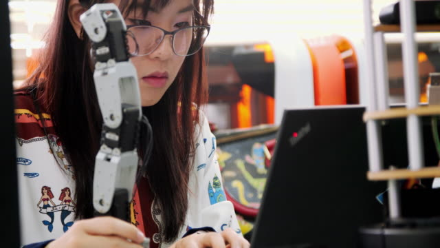 Teenage works on a fully functional programable Robot for her school robotics club project.Creative designer testing robotics prototype in workshop.Science concept