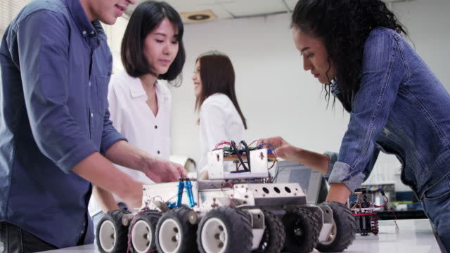 teenage works on a fully functional programable robot for robotics club project.creative designer testing robotics prototype in workshop.science concept - prototype stock videos & royalty-free footage