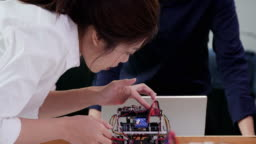 Teenage works on a fully functional programable Robot for robotics club project.Creative designer testing robotics prototype in workshop.Science concept