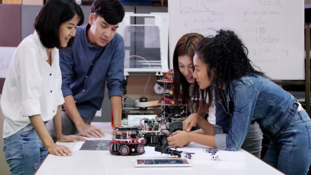 teenage works on a fully functional programable robot for robotics club project.creative designer testing robotics prototype in workshop.science concept - engineer stock videos & royalty-free footage