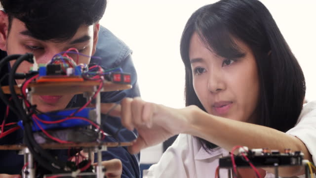 teenage works on a fully functional programable robot for robotics club project.creative designer testing robotics prototype in workshop.science concept - programmer stock videos & royalty-free footage