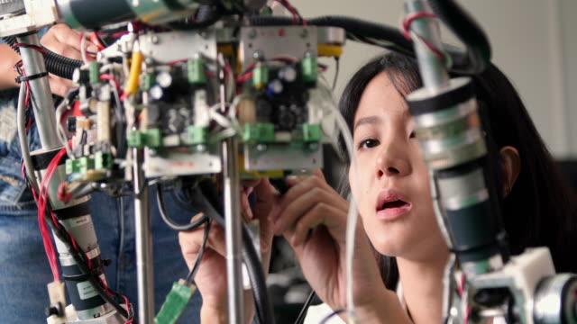 ロボット クラブの学校プロジェクトで完全に機能のプログラマブル ロボットの 10 代の作品。創造的なデザイナーは、ワーク ショップでロボットのプロトタイプをテストします。科学のコン - プロトタイプ点の映像素材/bロール