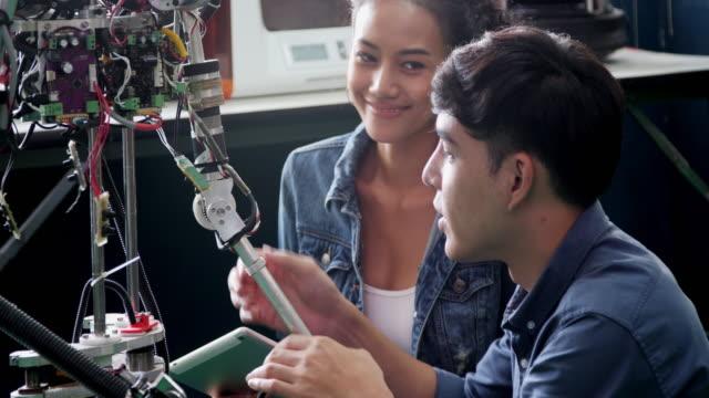vídeos de stock e filmes b-roll de teenage works on a fully functional programable robot for  school robotics club project.creative designer testing robotics prototype in workshop.science concept - modelo ocupação