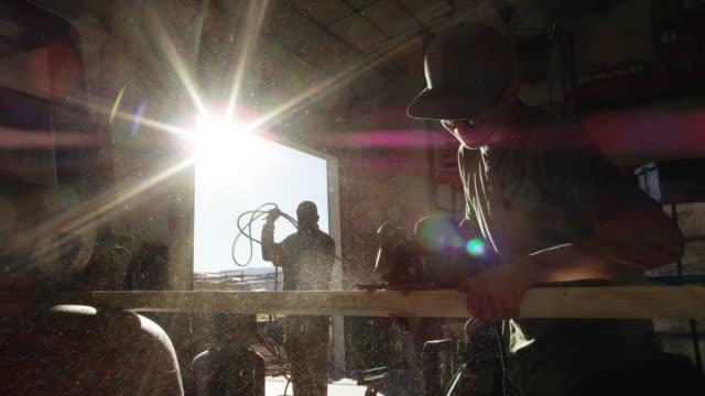 a teenaged caucasian boy cuts through a long, wooden plank with a circular saw in a bright manufacturing facility as sawdust flies through the air - un ragazzo adolescente video stock e b–roll