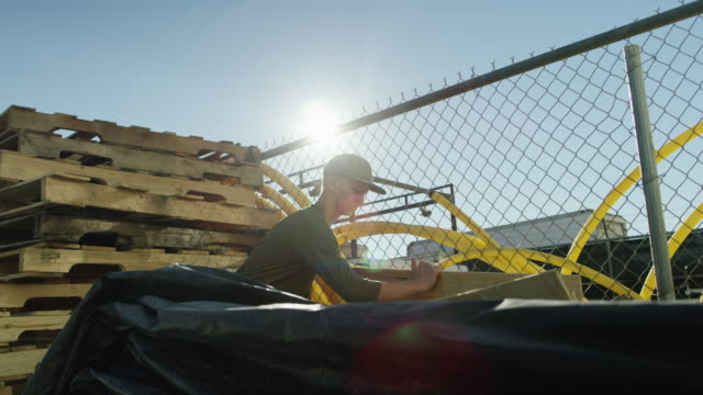 a teenaged caucasian boy lifts a large, wooden sheet in a manufacturing yard outdoors underneath a clear, blue sky - stereotypically working class stock videos & royalty-free footage
