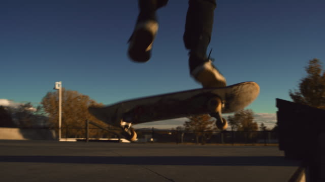 vídeos de stock, filmes e b-roll de um adolescente caucasiano executa um pé regular kickflip mais uma lacuna com seu skate no parque - proeza acrobática