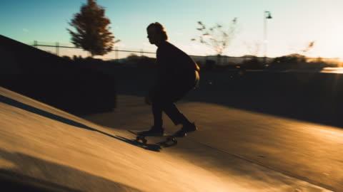 stockvideo's en b-roll-footage met een tiener kaukasische jongen voert een regelmatige voet kickflip over een kloof met zijn skateboard in het skatepark - skateboard