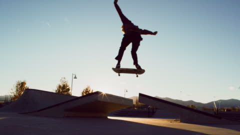 a teenaged caucasian boy performs a regular foot ollie over a gap with his skateboard at the skatepark - teenage boys stock videos & royalty-free footage