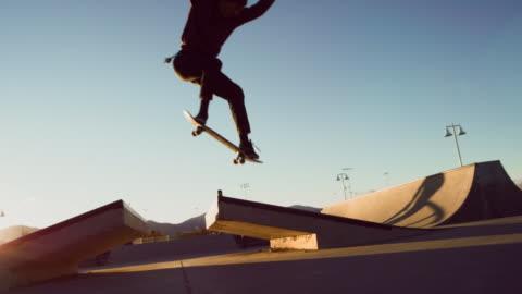 stockvideo's en b-roll-footage met een tiener kaukasische jongen voert een regelmatige voet ollie over een kloof met zijn skateboard in het skatepark - skateboard