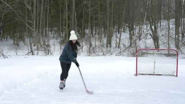teenaged girl playing hockey on frozen pond in winter. - アイスホッケー点の映像素材/bロール