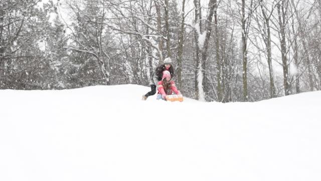 teenaged girls tobogganing in winter snowfall. - winter sport stock videos & royalty-free footage
