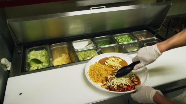teenaged hispanic cook adds cheese from a salad bar to a plate of vegetables, rice, and bacon-wrapped shrimp in a commercial kitchen at a mexican restaurant - guanto da chirurgo video stock e b–roll